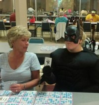 #33 Batman or another superhero playing bingo at a crowded recreation center.