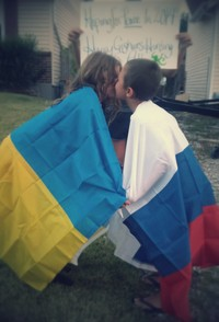 #44 Two people kissing across the Russia/Ukraine Boarder. If safety is a concern the image may be two people anywhere wrapped in a Russian and Ukrainian flag kissing each other.